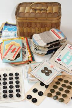 basket full of vintage sewing notions, needle books, carded yarn, thread, buttons