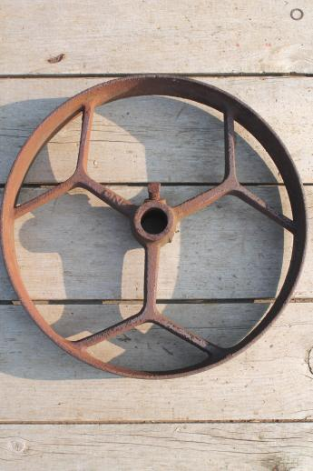 big old iron fly wheel from steampunk vintage industrial machinery or farm equipment