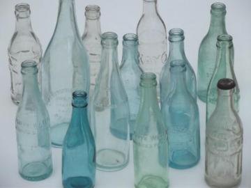 collection of old soda & water bottles, heavy clear glass & aqua blue glass bottles