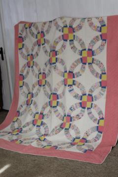 hand-stitched double wedding ring quilt, vintage cotton print fabrics w/ pink border