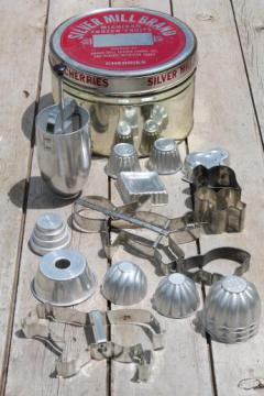 old cherry tin full of vintage cookie cutters, small jello molds, doughnut dropper