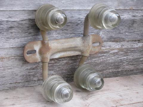 primitive harness or coat hook pegs, antique glass insulators on steel bracket rack
