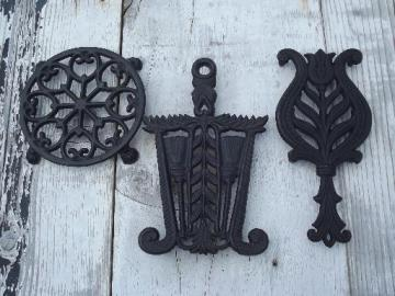 vintage Wilton cast iron kitchen trivets, round and iron shape trivet lot