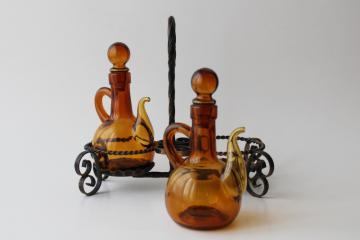 vintage hand blown glass cruet set, amber glass pitchers & stoppers in wrought iron stand