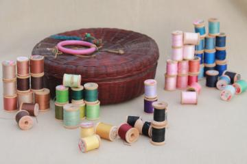 vintage round wicker sewing basket full of spools of colored cotton thread